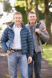 Two Male Friends Walking Outdoors In Autumn Park Royalty Free Stock Photos