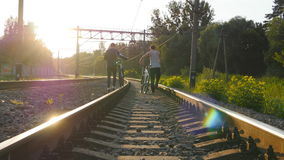 Two male friends walking with their bikes on the rails at the railway in sunset and talking. Two male friends walking with their bikes on the rails at the stock video footage