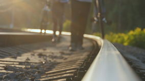 Two male friends walking with their bikes on the rails at the railway towards the camera. Dangerous and risky journey. Two male friends walking with their bikes stock footage