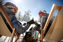 Two gay male friends toasting with bottles of beer. Two male gay friends on skiing toasting with bottles of beer in cafe outdoor Royalty Free Stock Photography