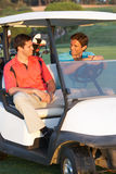 Two Male Golfers Riding In Golf Buggy Stock Images