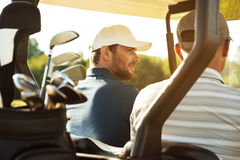 Two male golfers sitting in a cart. And talking Stock Image