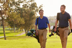 Two Male Golfers Walking Along Fairway Carrying Bags Royalty Free Stock Photos