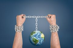 Two male hands bound together with chains and linked to an Earth globe between them. Bound by nature. Environment rules. Natural limits stock images