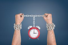 Two male hands bound together with chains and linked to a red retro clock. Slave of time. Time breaks all. Time loss royalty free stock images