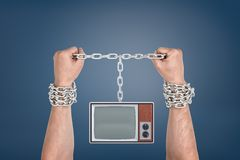 Two male hands bound together with metal chains and linked to a retro TV unit with blank screen. Bound by media. Information slaves. TV addiction stock image