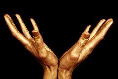 Two male hands in gold paint isolated. On a black background Stock Photo