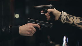Two male hands with guns take aim at each other. Close up.  stock video footage