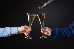 Two male hands holding champagne glasses and foil blowout Royalty Free Stock Photos