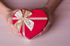 Two male hands holding red gift box in form of heart Stock Photos