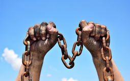Two male hands holding a rusty metal chain. Two dirty male hands holding a rusty metal chain, arms raised Stock Photo