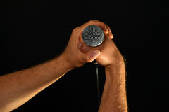 Two male hands with microphone isolated on black. Two male hands holding microphone with wire cable isolated on black background Royalty Free Stock Photography