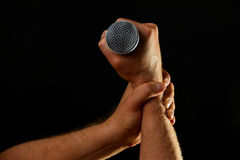 Two male hands with microphone isolated on black. Two male hands holding microphone with wire cable isolated on black background Royalty Free Stock Photos