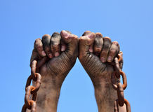 Two male hands are raised up. And holding a rusty chain Stock Photos