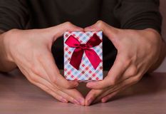 Two male hands in shape of heart holding checkered gift box with Stock Photography
