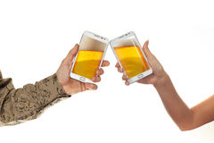 Two male hands in shirts hold smart phones with beer against white background stock image