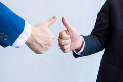 Two male hands showing thumbs up. On empty background Stock Photos