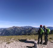 Two male hikers are pointing at the mountains far away and talking about what the names of those mountain are.  Royalty Free Stock Photography