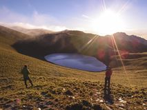 Two male hikers standing on a higher place by the Jiaming lake, and enjoying the beautiful sunrise. Two male hikers standing on a higher place by the Jiaming Stock Photography