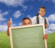 Two Male Hispanic Students with Thumbs Up and Chalk Board. Hispanic Students with Thumbs Up in Grass Field Holding Blank Chalk Board Royalty Free Stock Photography