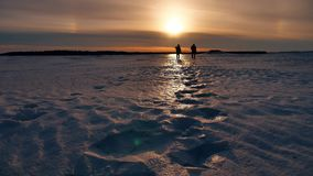 Two male man silhouette of the sunset hikers walking sunlight in untouched snow landscape. adventures journey trip. Two male man silhouette of sunset hikers stock video footage