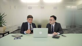 The two male managers discuss the report in co-working room with glass wall. They sit at the big light table with brand new laptop, tablet, calculator and stock video footage