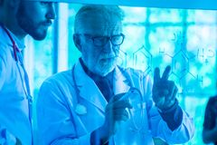 Two male medical doctors consulting each other on glass Board blue tone stock image