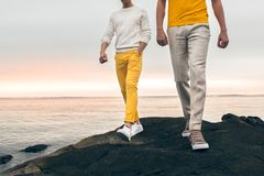 Two male models wearing fashionable spring summer outfit with colorful pants, t-shirt, sweater and shoes walking outdoors. On the rock ocean beach Royalty Free Stock Photo