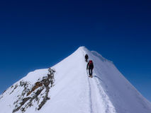 Two male mountain climbers on an exposed snow summit ridge in the Swiss Alps Stock Photo