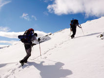 Two male mountain climbers with heavy backpacks on the way to the summit on a winter day Stock Photography