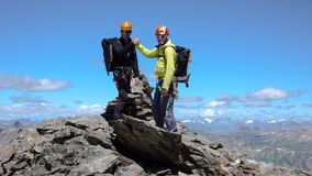 Two male mountain climbers on a summit in the Swiss Alps. Two male mountain climbers shake hands and congratulate each other on reaching a high summit in the Royalty Free Stock Photography
