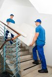 Two Male Movers Carrying Sofa On Staircase. Two Happy Male Movers In Uniform Carrying White Sofa On Staircase Royalty Free Stock Photography