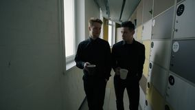 Two male office workers going through corridor with lockers. Concept of: business people, office corridor, management consulting, coffee drinking, locker room stock footage