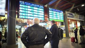 Two male passengers waiting for a train, checking timetable on display screen. Stock footage stock video footage