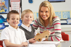 Two Male Primary School Pupils And Teacher Working. At Desk In Classroom stock photos