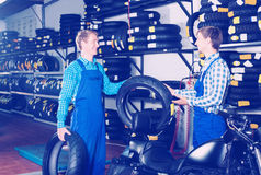 Two male professionals standing with new tires Royalty Free Stock Photos