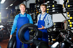 Two male professionals standing with new tires Stock Images