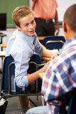 Two Male Pupils Talking In Class Stock Image