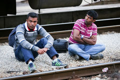 Two male refugees on railway tracks Stock Photos