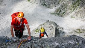 Two male rock climbers on a granite climbing route in the high alpine peaks of southeastern Switzerland Royalty Free Stock Photo