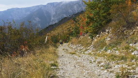 Two male runners run from hill on a mountain trail. Yalta, Russia - October 5, 2016: two male runners run uphill on a mountain trail during Crimea mountain stock video
