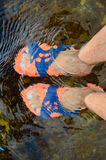 Two male's feet with orange and blue sandals in. Picture of two hunans feet with orange and blue sandals in water over flowing background Royalty Free Stock Images