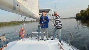 Two male sailors on deck of sailing yacht, friends, vacation. Stock footage stock video