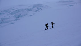 Two male ski mountaineers on a dark foggy morning in the Swiss Alps headed to the Strahlhorn. Near Saas Fee Stock Photos
