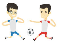 Two male soccer players fighting for ball. Two asian soccer players fighting over control of ball during a football match. Football players in action during Stock Photo