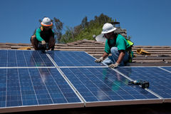 Two male solar workers install solar panels Stock Images