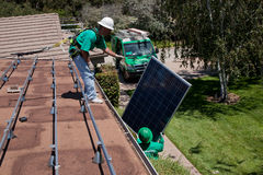 Two male solar workers install solar panels Royalty Free Stock Photos