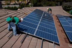 Two male solar workers install solar panels Royalty Free Stock Photo