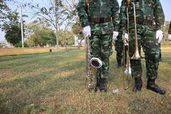 Two male soldiers stand holding an instrument Saxophone and trombone Lawn background royalty free stock photography