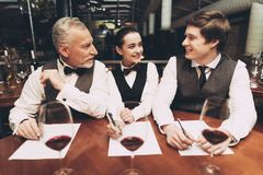 Two male sommeliers and female sommelier make up wine list sitting at table with glasses of wine. Confident sommelier tasting wine in restaurant royalty free stock photo
